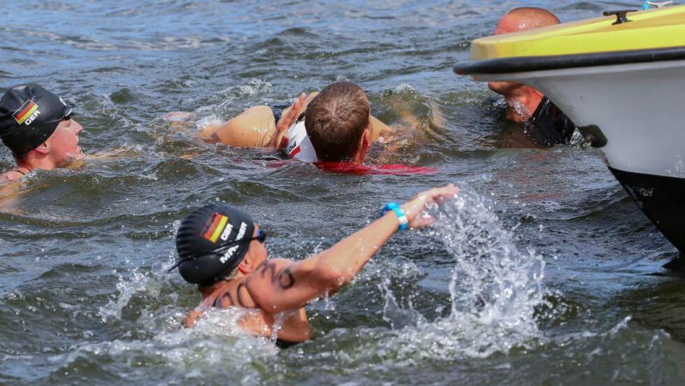 MÅTTE REDDES: Personer svømmer for å redde Natalia Charlos som kollapset under EM i Berlin. Foto:  EPA/MICHAEL KAPPELER