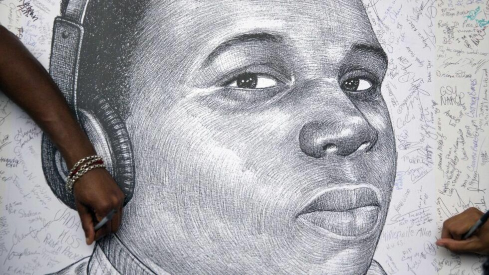 SYMBOL: Demonstranter skriver sine navn på en tegning av den drepte Ferguson-tenåringen Michael Brown, som 9. august ble skutt seks ganger og drept av en politimann. Nok en gang blusser opptøyer med raseundertoner opp i USA, og nok en gang stilles det spørsmål om politibrutalitet og strukturell rasisme i politiet. Foto: David Goldman / AP