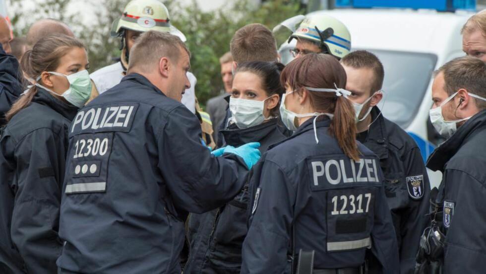 FORHOLDSREGLER: Politifolk ifører seg munnbind utenfor arbeidsformidlingssenteret i Prenzlauer Berg der den 30-årige kvinnen kollapset tidligere i dag.  Foto: MAURIZIO GAMBARINI / EPA / NTB SCANPIX