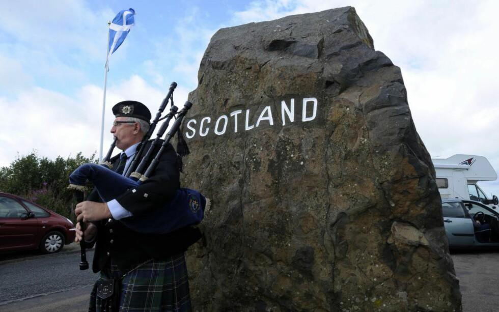 GRENSESTEIN: En skotte spiller sekkepipe ved en grensestein mellom England og Skottland, som igjen kan komme til å markere ei internasjonal grense. Skottene skal ha folkeavstemning om å gå ut av Storbritannia. Spørsmålet er om et uavhengig Skottland kan regne med å fortsette innenfor EU. Foto: AFP / Scanpix / ANDY BUCHANAN