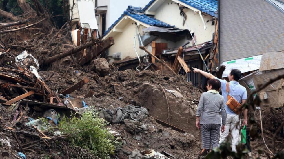 TATT AV JORDSKRED:  Beboere i det jordskredrammede området i Hiroshima ser etter restene av sine hjem søndag formiddag. Dødstallet har passert 50, og 38 er savnet - samtidig som 164 000 mennesker lever med evakueringsvarsel. Foto: Jiji Press, AP/NTB Scanpix.