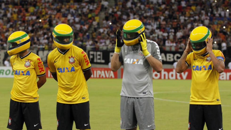HYLLET SENNA: Fotballspillere på det brasilianske laget Corinthians markerer 20-årsjubileumet for Ayrton Sennas død ved å hylle formel 1-legenden med å stille seg opp i formel 1-hjelm før kampen mot Nacional. Foto: Bruno Kelly / NTB Scanpix