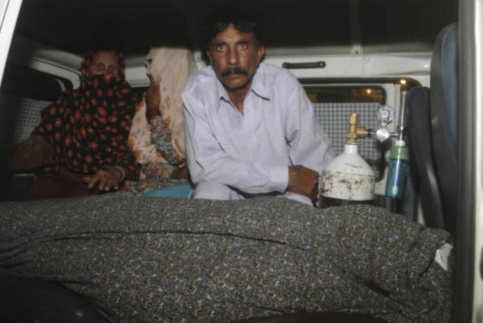 ANGREPET: Mohammad Iqbal sitter i ambulansen ved siden av liket av sin gravide kone som ble steinet til døde av sin egen familie i Lahore i Pakistan i går. Foto: AP/K.M. Chaudary/NTB Scanpix