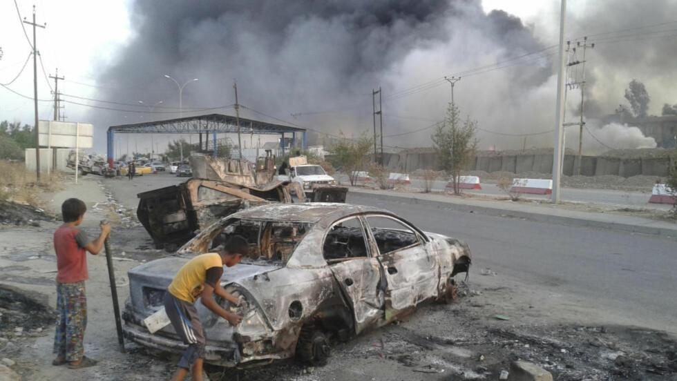 VOLDSOMME KAMPER:  Irakiske barn sjekker ut en nedbrent bil. LIke bortenfor er voldsomme kamper mellom irakiske sikkerhetsstyrker og den al-Qaida-linkede gruppa ISIL, som nå har tatt over byen Mosul. Foto: Reuters/Scanpix