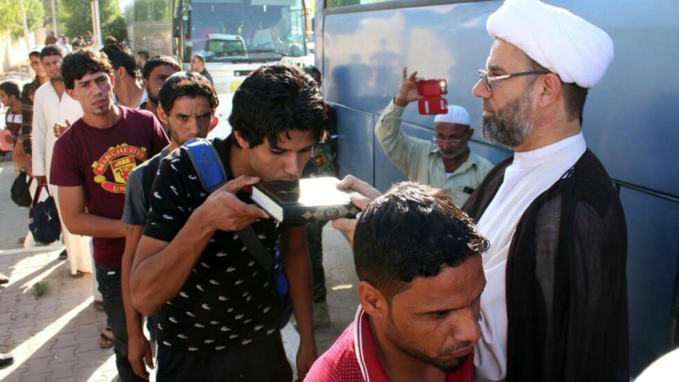 TIL KAMP:  Frivillige irakere har meldt seg til å delta i kampen mot ISIL. Her kysser de Koranen før de legger ut på den lange bussturen fra Basra i sør til Mosul lenger nord. Foto: AFP / NTB Scanpix