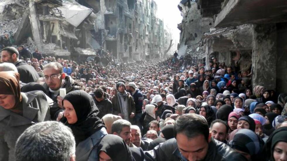 IKONISK BILDE:  Verden ble sjokkert da FN sendte ut dette bildet av innbyggere i Yarmouk som står og venter på å få utdelt mat etter å ha levd på gress, oliven, katter og hunder i månedsvis på grunn av voldsomme kamper i leiren. Bildet ble sendt ut i januar i år. Siden den gangen har knapt situasjonen blitt noe bedre for innbyggerne. Men de har ingen steder å dra: Ikke noe land sier ja til å gi dem visum. Foto: UNRWA/Ap/Scanpix