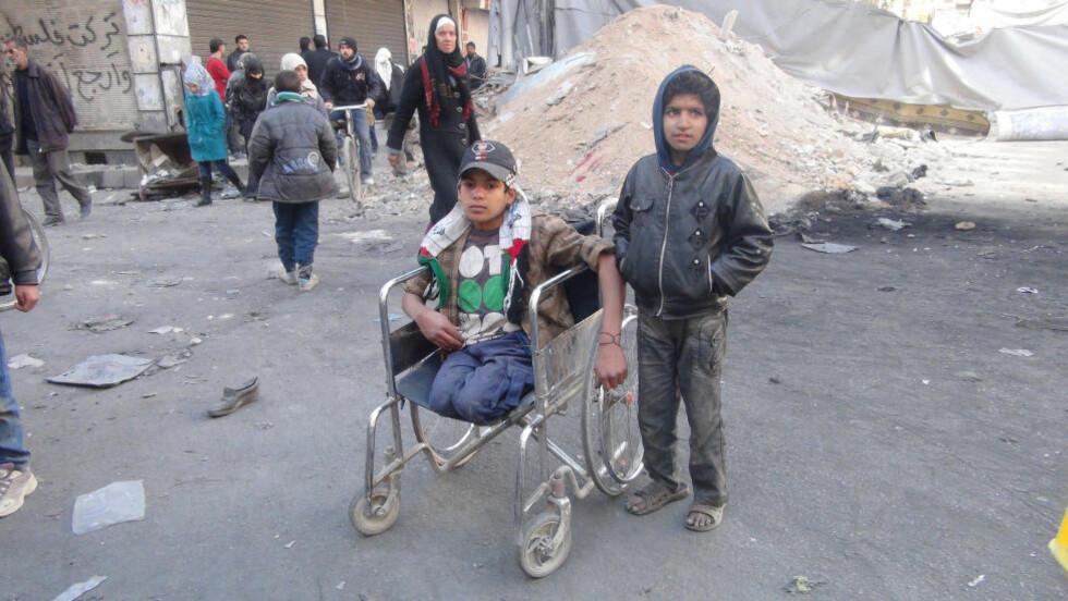 HÅPLØS SITUASJON:  De palestinske syrerne i flyktningleiren Yarmouk, like utenfor Damaskus, har ingen steder å dra. Jordan og Tyrkia nekter palestinerne innreise, og det blir også stadig vanskeligere for innbyggerne å dra til Libanon. Dermed er palestinerne tvunget til å være igjen i den krigsherjede flyktningleiren. En rekke av innbyggerne er underernært og har enorme sjokkskader etter harde kamper i leiren de siste årene. Foto: UNWRA