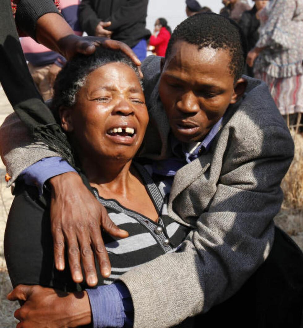 I SORG: En slektning av en av de rammede under Marikana trøstes under en minnestund i august 2012. Foto: Reuters / NTB scanpix