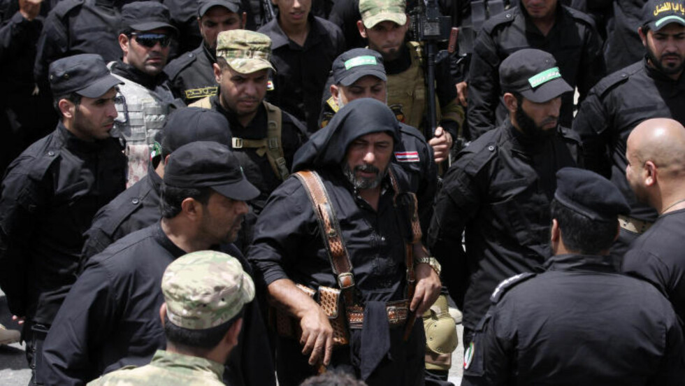 KLARE FOR KAMP:  Mannen i midten er en av lederne i den fryktede sjia-militsen Mehdi, og blir kalt Abu Deraa. Sjia-ene fra Sadr-byen er nå klare for å kjempe mot ISIL. Foto: Wissm al-Okili/Reuters/Scanpix