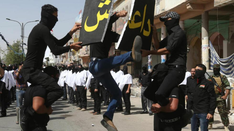 VISER MUSKLER:  Et maskert sjia-milits-medlem sparker i stykker et skilt hvor det står navnet til den beryktede gruppa Den islamske stat i Irak og Levanten (ISIL), som sjiaene nå gjør seg klare til å kjempe mot. Foto: Hussein Malla/Scanpix