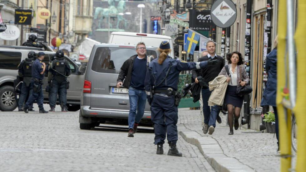 FULL ALARM: Folk evakueres løpende fra et av flere rammede bygg under bombealarmen i Stockholm torsdag. Foto: Reuters / NTB scanpix