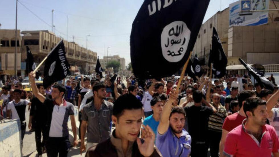 STØTTE-DEMONSTRASJON:  Mandag denne uka gikk en rekke innbyggere i Mosul i tog for å vise sin støtte til organisasjonen Den islamske stat i Irak og Levanten, som tok over byen for snart to uker siden. ISIL tok i helga over en rekke byer i Irak. Foto: Ap/Scanpix
