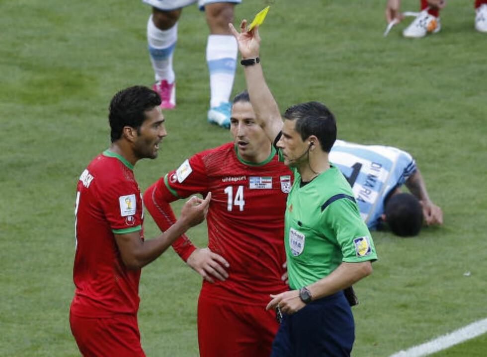 GULT KORT: Dommer Milorad Mazic dro fram det gule kortet da iranske spillere klaget på avgjørelsen. Foto: REUTERS / Leonhard Foeger / NTB SCANPIX