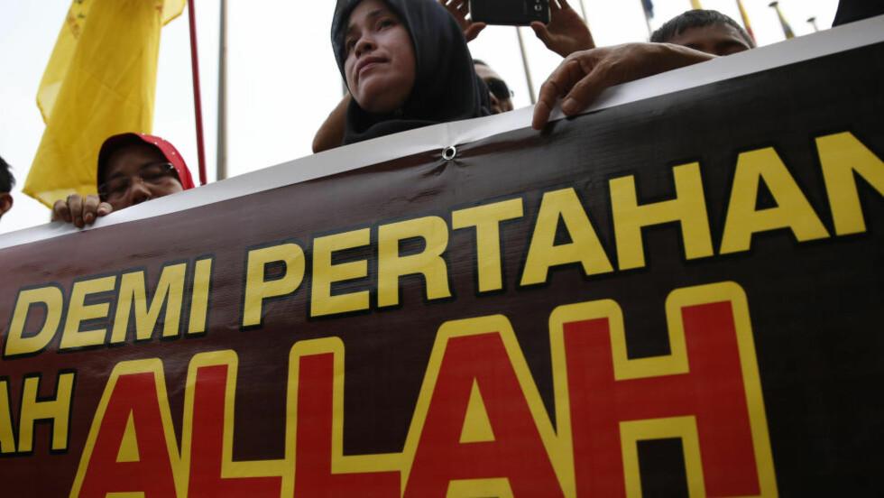 DEMONSTRERER: En muslimsk kvinne holder et banner utenfor Malayias høyesterett. Foto: Vincent Thian / AP / NTB Scanpix