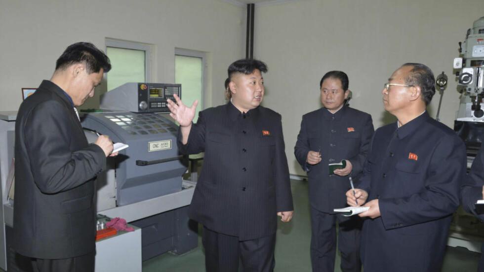 SVEISEN DIKTATOR: Nord-Koreas leder Kim Jong-un vil pålegge alle å ha hans hårsveis. Her ser Kim Jong-un på en mann som er litt tynn i håret, mens han er på en inspeksjon av en fabrikk i Nord-Korea. Foto: Reuters/KCNA/NTB Scanpix