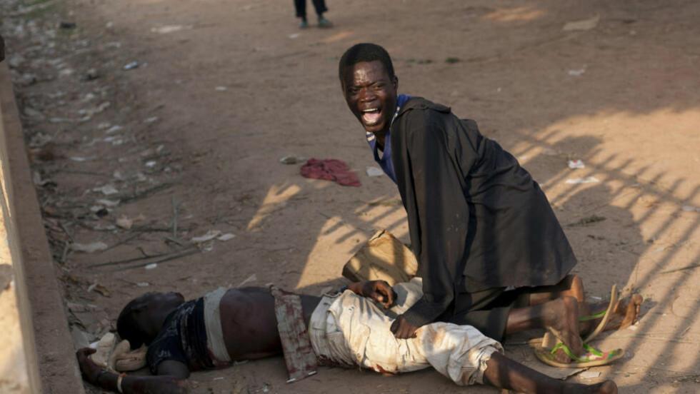 GRUSOM SITUASJON: En ung mann forsøker å hjelpe sin ifølge nyhetsbyrået AP hardt skadde kamerat, etter at soldater fra Tsjad skal ha skutt på ham etter en demonstrasjon ved flyplassen i Bangui lille julaften. Foto: AP / NTB scanpix
