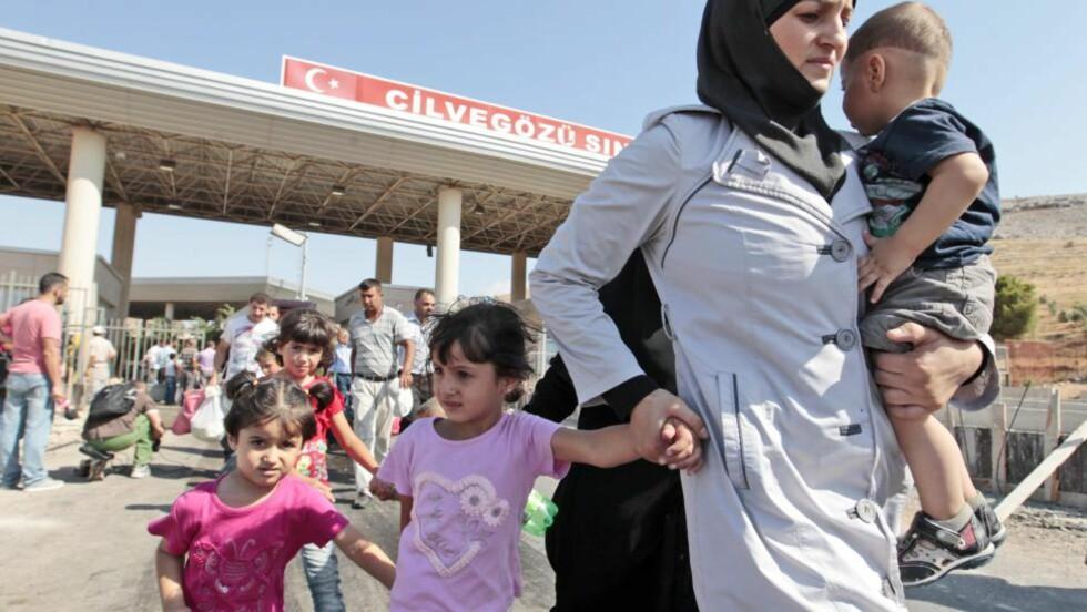 MILLIONER PÅ FLUKT:  Siden borgerkrigen i Syria startet for mer enn to år siden, har minst seks millioner mennesker blitt tvunget på flukt, i tillegg til at over 100.000 mennesker er drept og langt flere skadd. Her er syriske flyktnigner på vei ut til Tyrkia via Cilvegozu-grensa. Nå frykter den norsk-somaliske familiefaren at jentene hans er på vei inn i landet som folk flest flykter fra. Foto: Gregorio Borgia/Ap/Scanpix