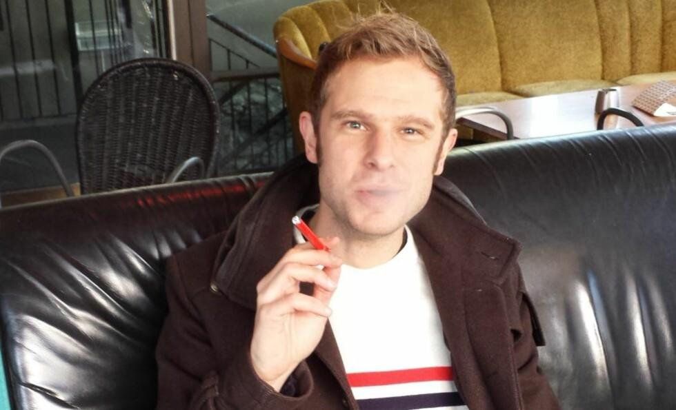RØYKESTOPP: Stortingsrepresentant Snorre Valen (SV) er sjøl sigarettrøyker og håper nikotinholdige e-sigaretten blir lovlig i Norge i nærmeste framtid. Her nyter han en fullt lovlig nikotinfri e-sigarett i Trondheim torsdag. Foto: Privat