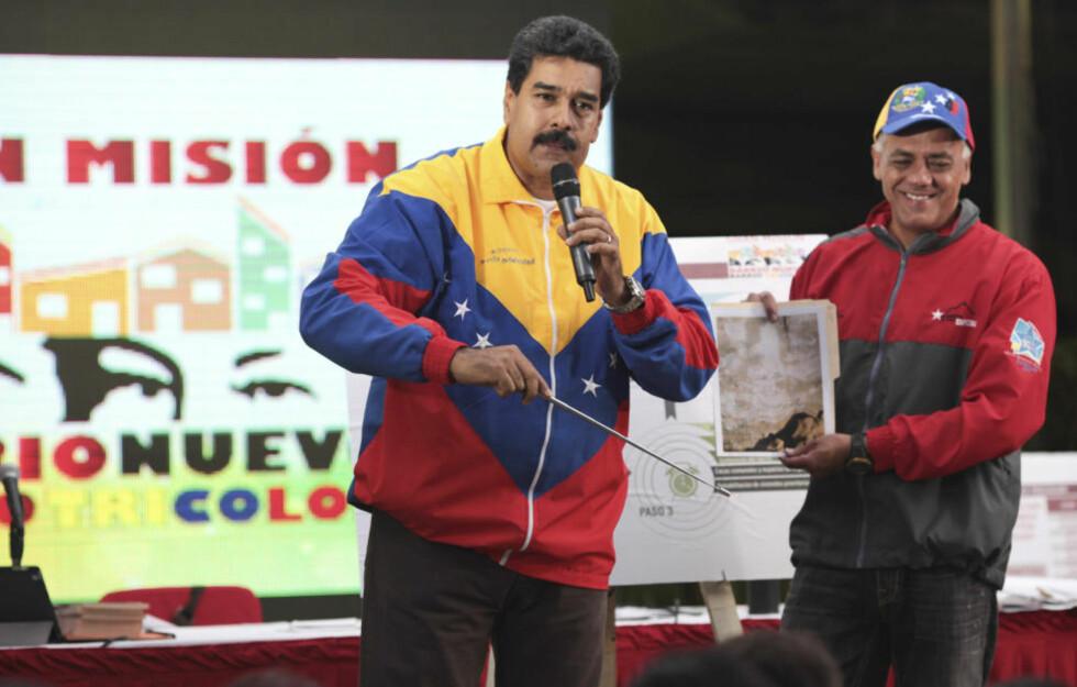 ET UNDER? President Nicolás Maduro viser et bilde fra fjellveggen i en metro-tunell hvor man mener å se ansiktet til avdøde Hugo Chávez. Til ære for Chávez har han nå utnevnt en viseminister for den høyeste sosiale lykke. Foto: REUTERS / Scanpix / Presidentpalasset Miraflores
