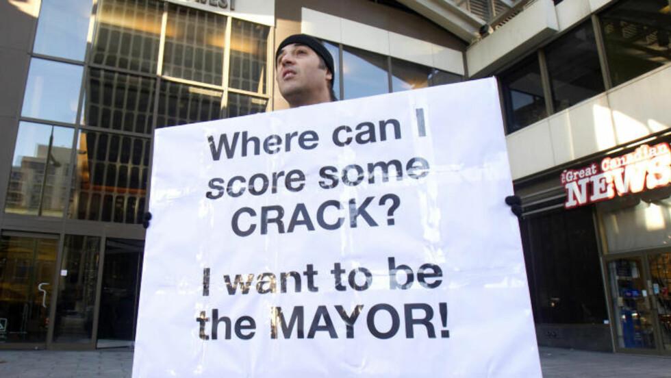 LATTERLIGGJORT: Nic Bibassis holder opp et skilt i Toronto med ordlyden: Hvor kan jeg kjøpe crack? Jeg vil bli ordfører. Foto: REUTERS/Fred Thornhill/Files