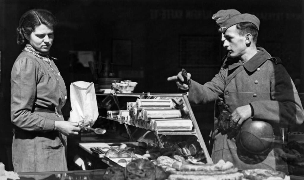 HVERDAG UNDER OKKUPASJON: Man tror gjerne Norges kamp mot Nazi-Tyskland startet 9. april, men helt slik var det ikke. Sommeren 1940 var det rettslig og faktisk usikkerhet om landets krigstilstand, skriver Hans Fredrik Dahl. Bildet viser en tysk soldat hos et Oslo-bakeri i aprildagene. Foto: NTB Scanpix.