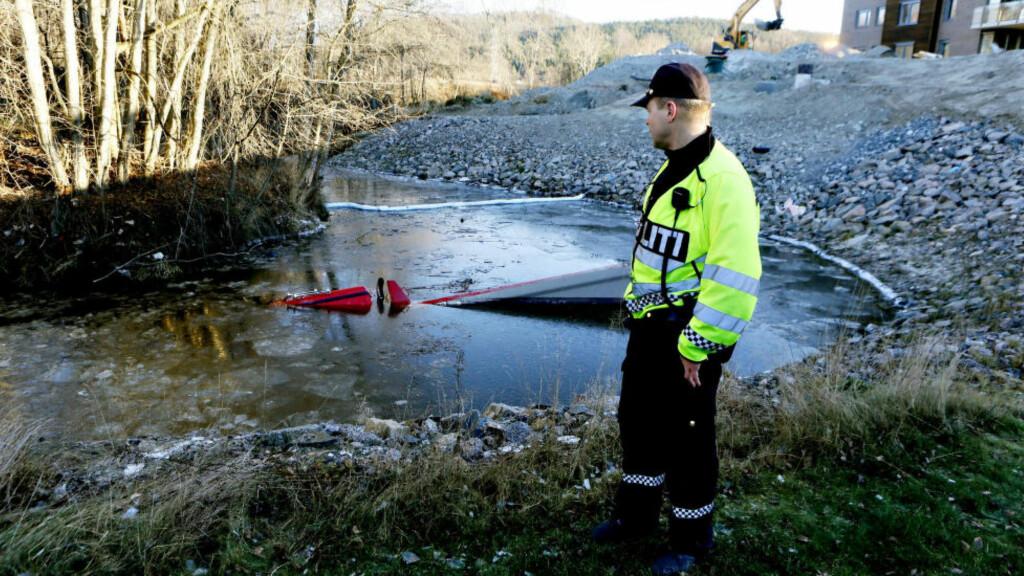 TRILLET: Lastebilen begynte å trille da sjåføren stod bak den. Nå jobbes det med å få den ut av vannet. Her politibetjent Olav Lundeberg. Foto: Torbjørn Berg / Dagbladet