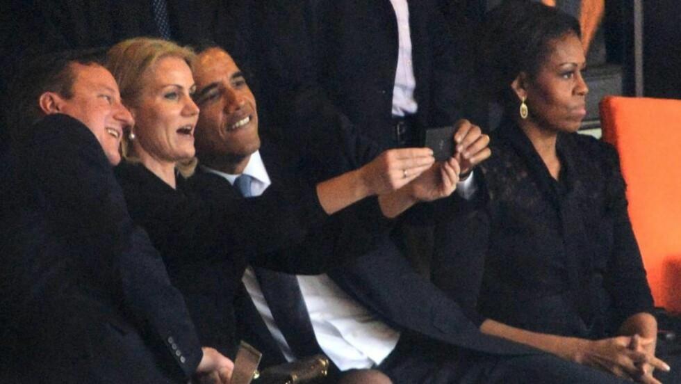 SELFIE: Her tar Helle Thorning-Schmidt (i midten) selfie sammen med USAs president Barack Obama (t.h) og den britiske statsministeren David Cameron. TIl høyre sitter førstedame Michelle Obama. Foto: AFP Photo/Roberto Schmidt/NTB Scanpix