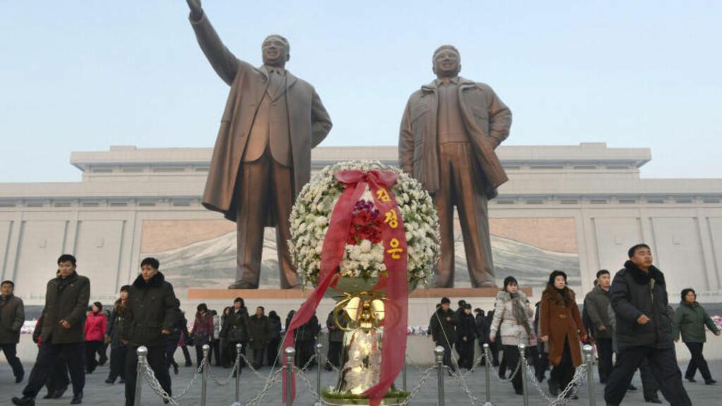 MINNEMARKERING:  Her legger flere ned blomster ved statuene av Kim Jong-il og Kim Il-Sung i Pyongyang. Foto: Reuters.