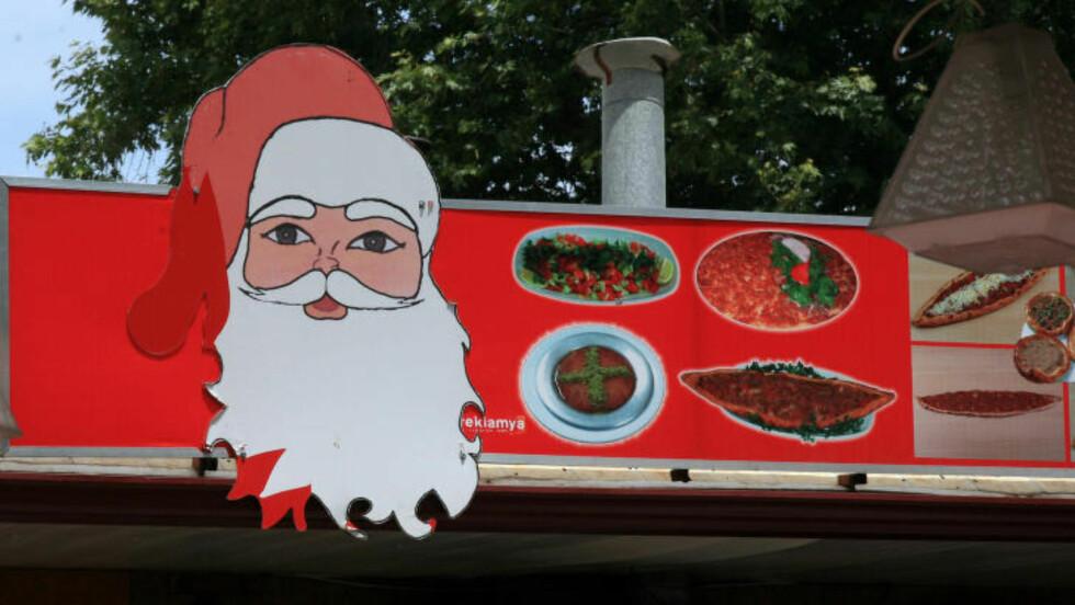 NISSEMAT: Du er aldri i tvil om at du befinner deg i julenissens hjemby når du beveger deg rundt i kystbyen Demre. Her er nissens kontrafei brukt i reklameplakat for lokal tyrkisk mat. Foto: EIVIND PEDERSEN