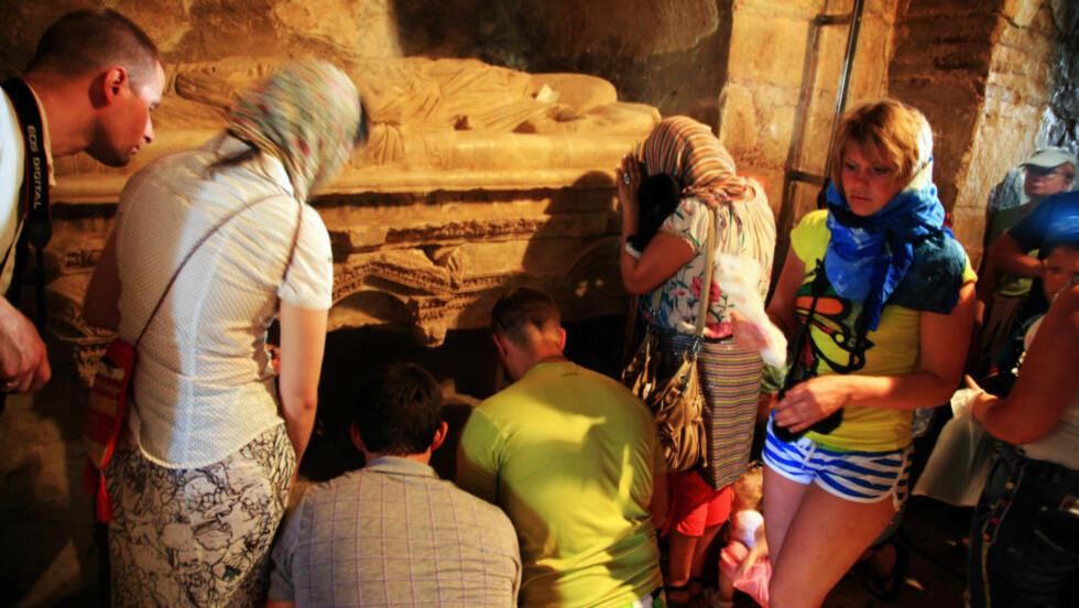 HVILESTED:  I denne sarkofagen hviler erkebiskop Nicholas. De mange pilegrimsreisende viser sin ære ved å bøye sitt hode og legge hånden på beskyttelsesglasset foran gravstedet. Foto: EIVIND PEDERSEN