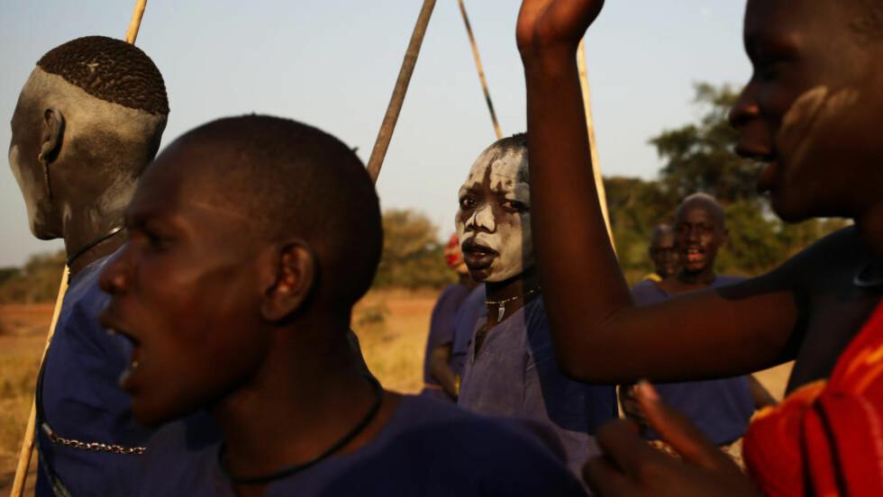 FORBANNET: Unge dinka-menn danser og roper ut i frustrasjon og sinne ved Rumbek, sentralt i Sør-Sudan. Det nærmer seg full borgerkrig i landet - og det blir stadig vanskeligere å drive legitim næring, som kvegdrift - disse unge mennenes levevei. Foto: Reuters / NTB scanpix
