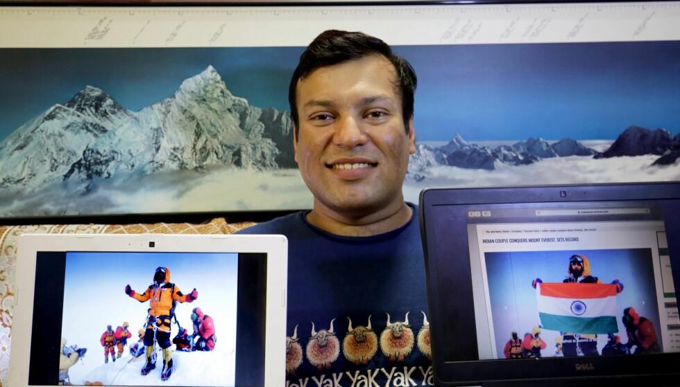 HAN VAR PÅ TOPPEN: I høyre hånd holder Satyarup Sidhantha originalbildet av seg selv fra Mount Everest. I venstre hånd holder han et av de manipulerte bildene hvor det framstilles som om det indiske paret var på toppen. Foto: Piyal Adhikary / EPA / NTB Scanpix