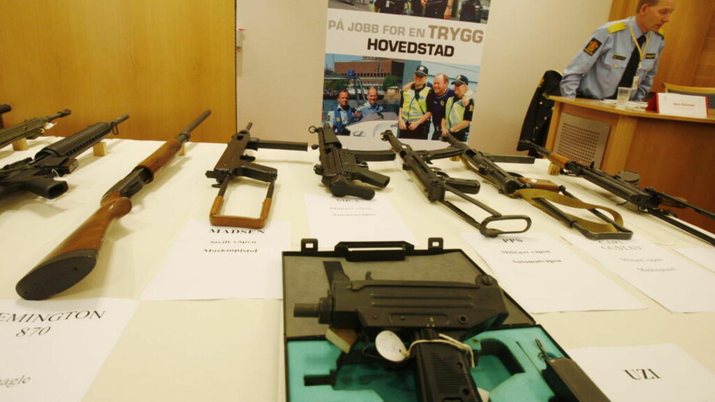 BESLAG: Våpen beslaglagt fra forskjellige gjenger, ligger foran visepolitimester Hans Halvorsen under en presssekonferanse hos Oslo politidistrikt i 2007. Foto: Lise Åserud / SCANPIX .
