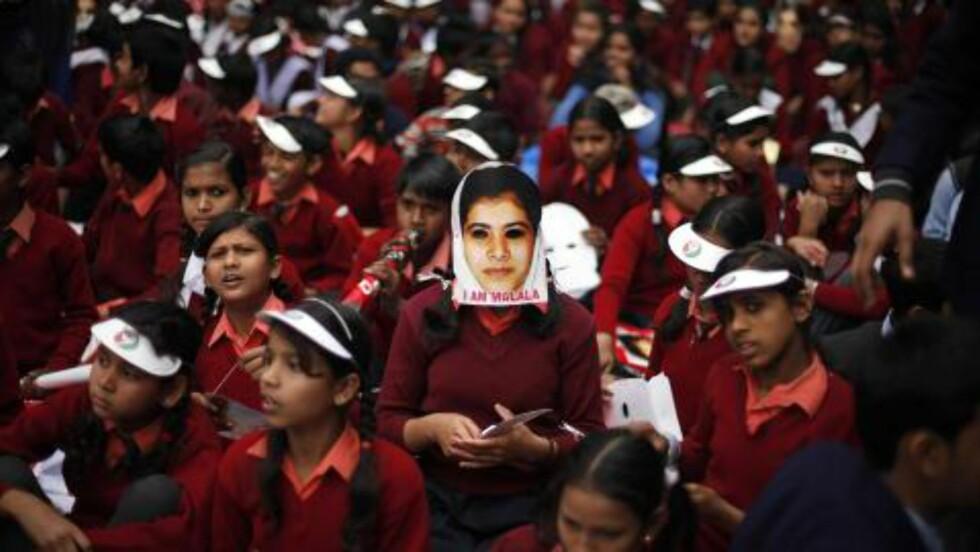 STØTTE VERDEN OVER:  En indisk skolejente har på seg en maske som skal forestille Malala Yousufzai, jenta som ble skutt av Taliban for ett år siden. Nå er Malala en av favorittene til Nobels fredspris. Foto: Altaf Qadri / Ap / Scanpix