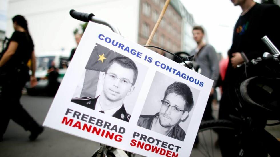 SMITTSOMT MOT:  Demonstranter med plakater med bilder av varslerne Bradley Manning (t.v.) og Edward Snowden. Til tross for folkelig støtte er de begge temmelig alene og utstøtt for å ha rystet systemet i verdens største supermakt. Foto:  EPA/KAY NIETFELD/NTB Scanpix