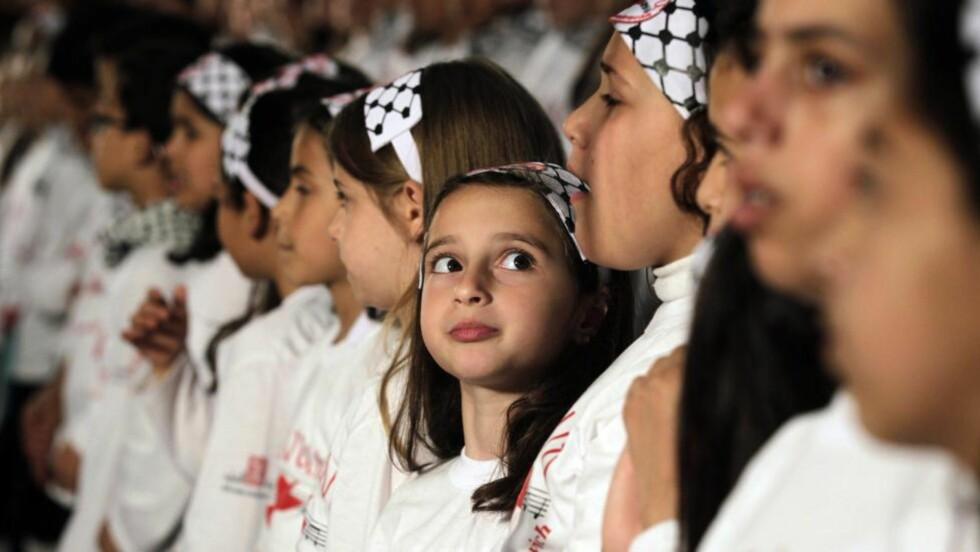 MEKTIGE SAKER: En ung palestinsk jente ser opp under en FN-kongress der koret hennes deltok. Nå har ny forskning vist hvordan korsang forener kroppenes egen rytme. Foto: Mohammed Abed / AFP / NTB Scanpix