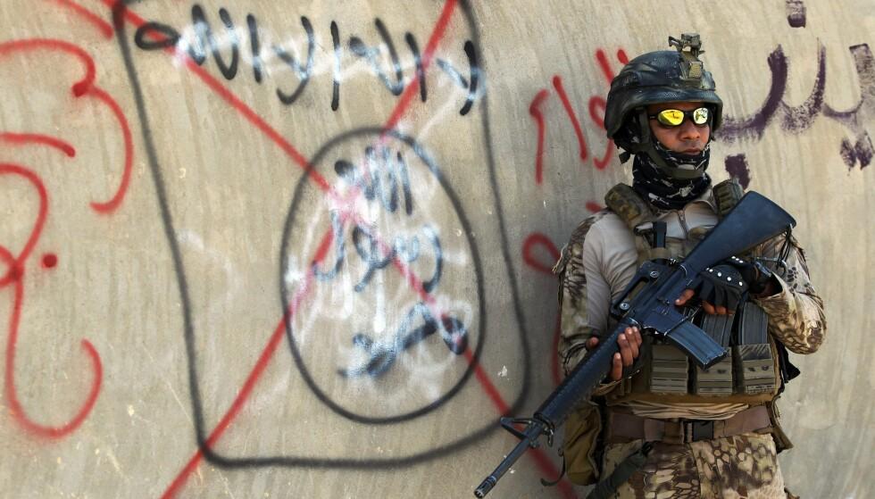 GRAFITTI: En irakisk soldat står foran en murvegg hvor noen har tagget et rødt kryss over IS-symbolet. Foto: AFP NTB Scanpix.