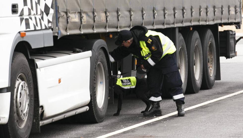 PÅ GRENSA: En toller med en av sine firbeinte medarbeidere inspiserer et vogntog på oppstillingsplassen på Tollvesenets grensestasjon på Svinesund. Illustrasjonsfoto: Heiko Junge / NTB scanpix