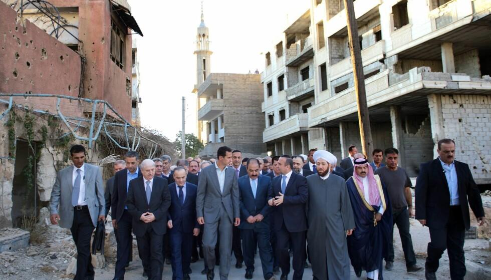 VI SKAL TA TILBAKE ALT: Den syriske presidenten Bashar al-Assad (midten) dukket i dag opp i Daraya, som inntil august var kontrollert av opprørerne. Assad sier nå at han og regimet skal kontrollere hele Syria. Foto: Sana / Afp / Scanpix