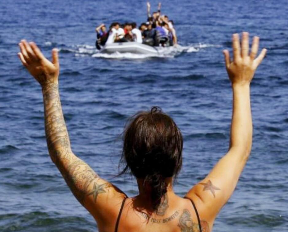 LESVOS: Syriske flyktninger ønskes velkommen til stranda på Lesvos av en av de frivillige som deltok sammen med artikkelforfatteren i september i fjor. 4000 nye flyktninger ankom øya hver dag. Foto: Privat
