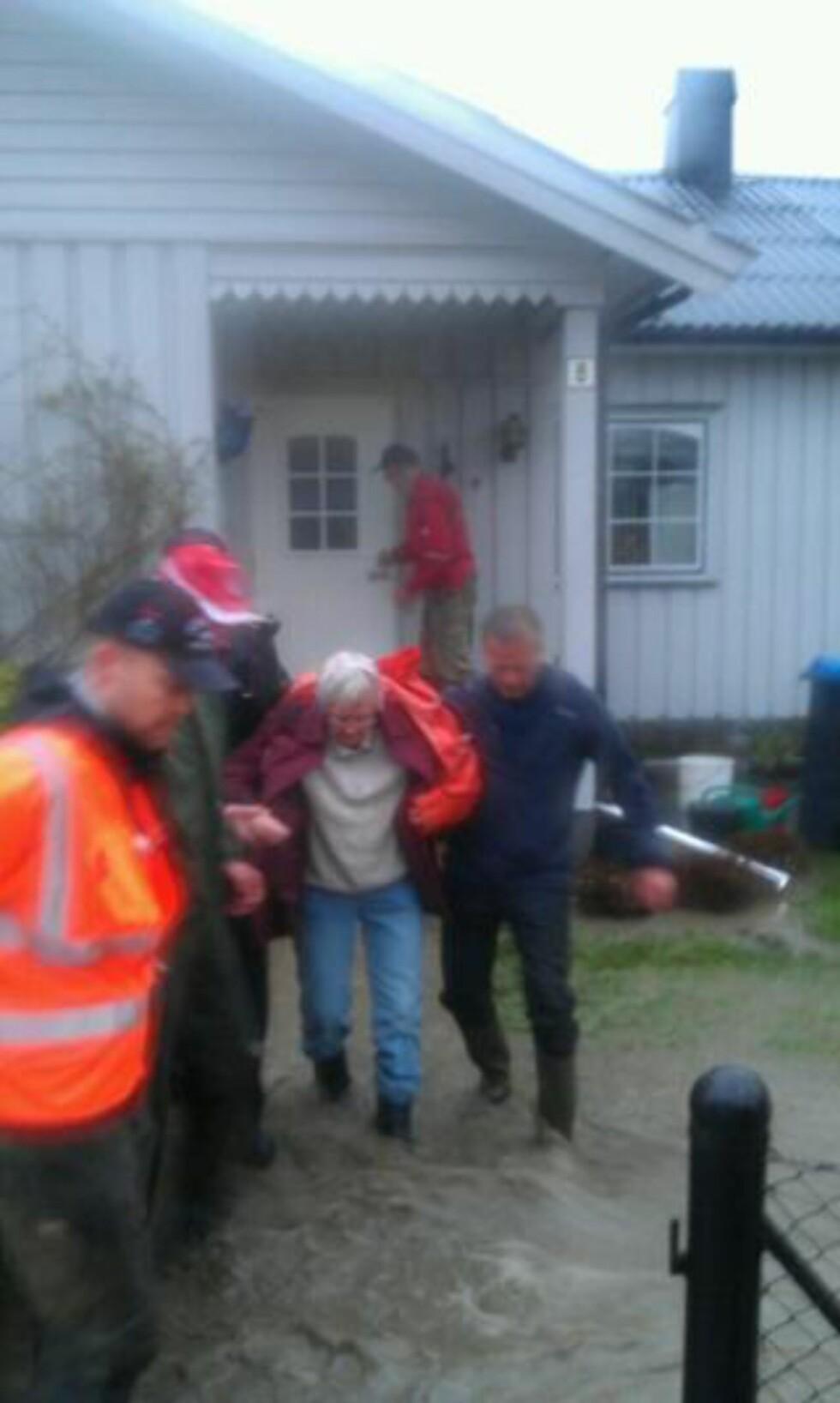 HJELPES I TRYGGHET:  Mannskaper hjelper denne kvinnen å komme i sikkerhet fra vannmasser mot hjemmet i Kvam sentrum onsdag kveld. FOTO: TONE SIDSEL SANDEN/DØLEN.