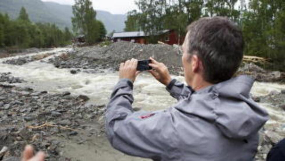 ETTER STORFLOMMEN I 2011:   Statsminister Jens Stoltenberg besøkte Kvam 12. juni 2011 etter storflommen da, og dokumenterte skadene med eget mobilkamera. Nå kan han ta nye bilder av sikringstiltakene fra den gang, som  ikke viste seg gode nok. Arkivfoto: Thomas Winje Øijord / NTB Scanpix.