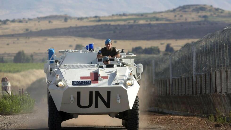 GOLAN DELT: Fredsstyrken UNDOF patruljerer langs gjerdet som skiller Israel og Syria på de delte Golan-høydene, like ved den delte landsbyen Qunteira. Når Østerrike nå trekker sine soldater ut, ber FN om nordisk hjelp. Foto: AFP / Scanpix / MENAHEM KAHANA