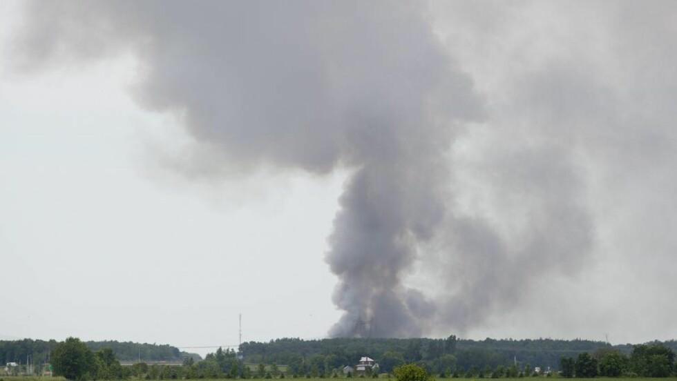 KRAFTIGE EKSPLOSJONER:  Svart røyk veltet i ettermiddag opp fra fyrverkerifabrikken i Coteau di Lac ved Quebec. Foto: Graham Hughes / The Canadian Press / AP / NTB SCANPIX
