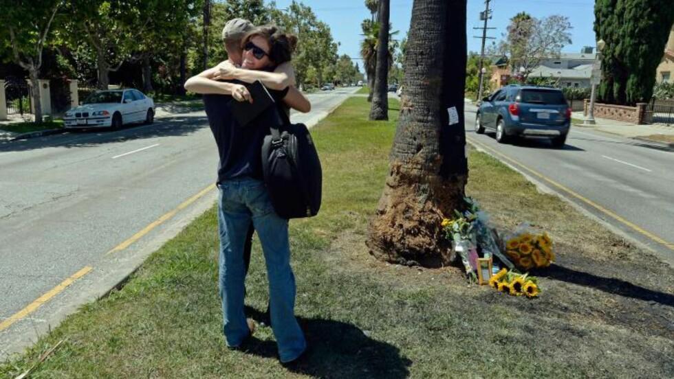 KRASJET, BILEN TOK FYR: Michael Hastings krasjet inn i dette treet i Hancock Park, Los Angeles, tirsdag. Bilen tok så fyr. På åstedet er det lagt ned blomster, bilder og minneord. Foto: NTB Scanpix