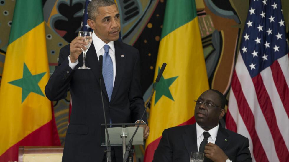 AFRIKA-TUR: Barack Obama skåler under en offisiell middag med presidenten i Senegal, Macky Sall. Foto: Evan Vucci / AP Photo
