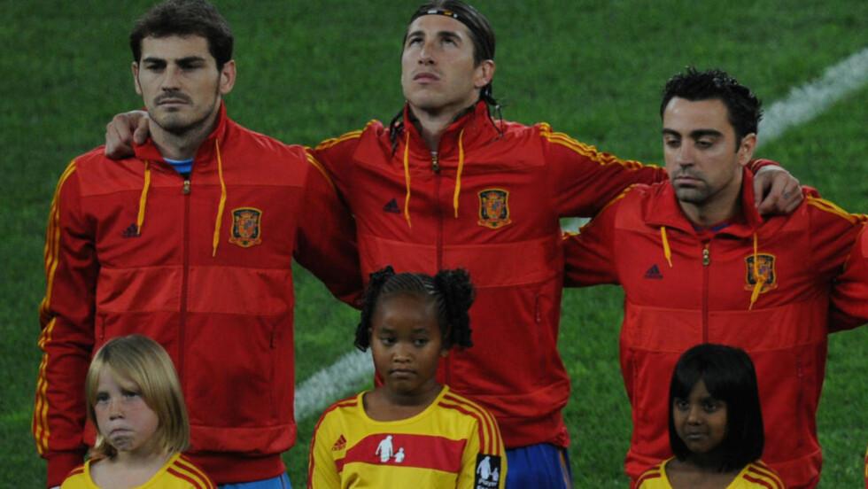 FØRER SEG INN I REKKENE: Sergio Ramos (midten) kan få sin 100. landskamp for Spania fredag. Da fører han seg inn i rekkene sammen med Iker Casillas (venstre) og Xavi (høyre). Foto: AFP / PEDRO UGARTE