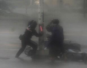 FORSØKTE Å HJELPE: Her forsøker en person å hjelpe en mopedist i Kaohsiung, Taiwan. Der slo Meranti til onsdag. Foto: EPA/RITCHIE B. TONGO/NTB Scanpix