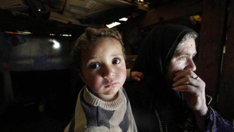 FLYKTER: Her er en bestemor med barnebarnet, som ifølge henne ble født på samme dagen som konflikten startet. Barnebarnet er nå ett år. Ifølge FN har nå mer enn én million flyktet fra det krigsherjede landet. Foto: AFP/JOSEPH EID/NTB SCANPIX