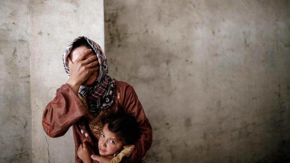 HAR KARTLAGT OVERGREP: Organisasjonen Woman under siege har i samarbeid med blant andre journalister, aktivister, forskere og leger kartlagt hvordan mennesker har blitt utsatt for seksuelle overgrep i Syria. Her gråter en kvinne mens hun holder sin datter under et bombeangrep i den syriske byen Aleppo septemberg 2012. Foto: AFP/SAM TARLING/NTB SCANPIX